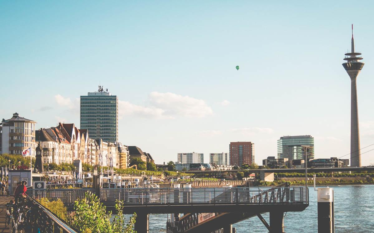 Board walk in Dusseldorf in Germany alongside river Rhine. The sun is shining.