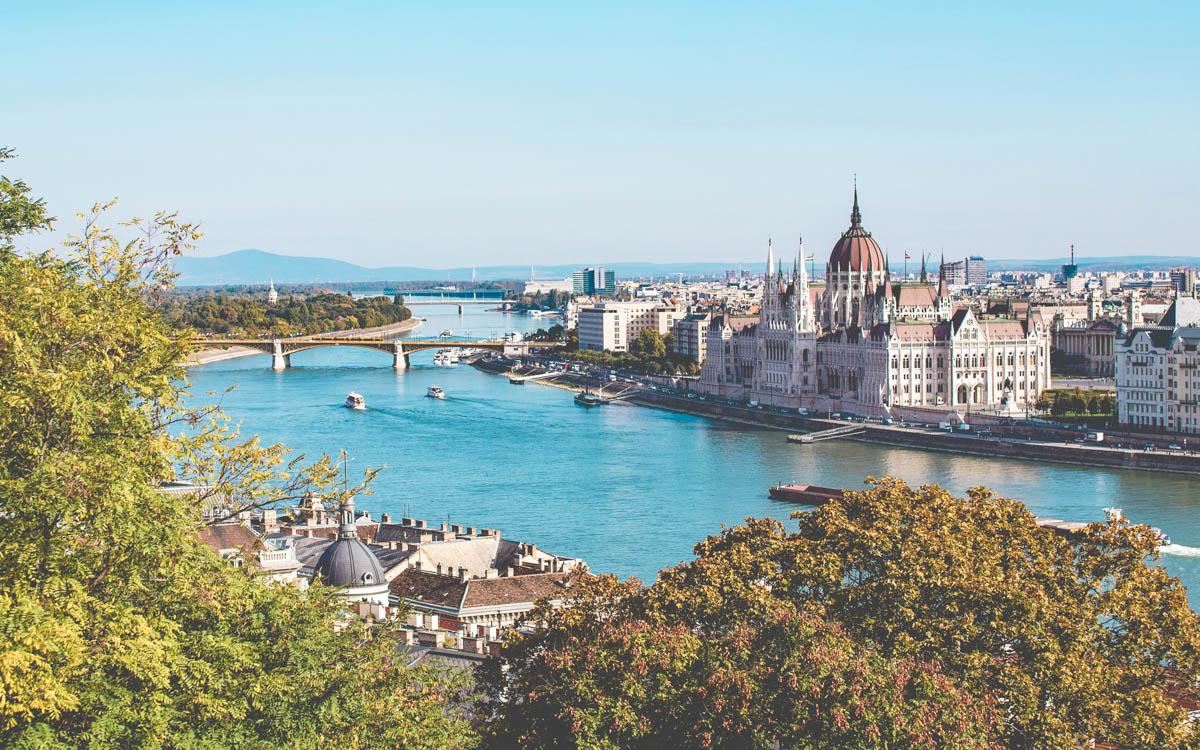 Utsikt över floden Donau i Budapest Ungern. Solen lyser på husen längs floden. Broar länkar samman de två stadssidorna.