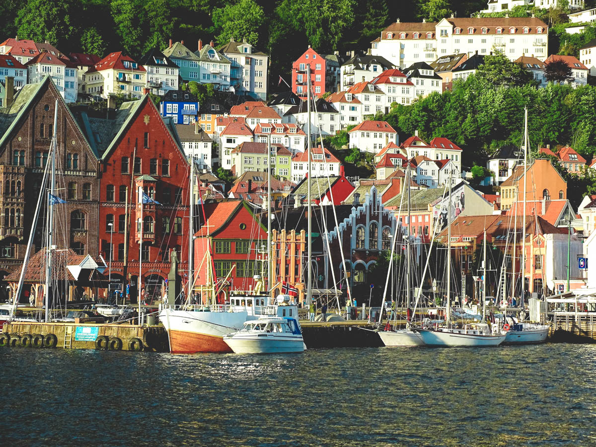 boats by the famous port of bergen, bryggen. on the steep hills next to the port beautiful and colorful houses are built.
