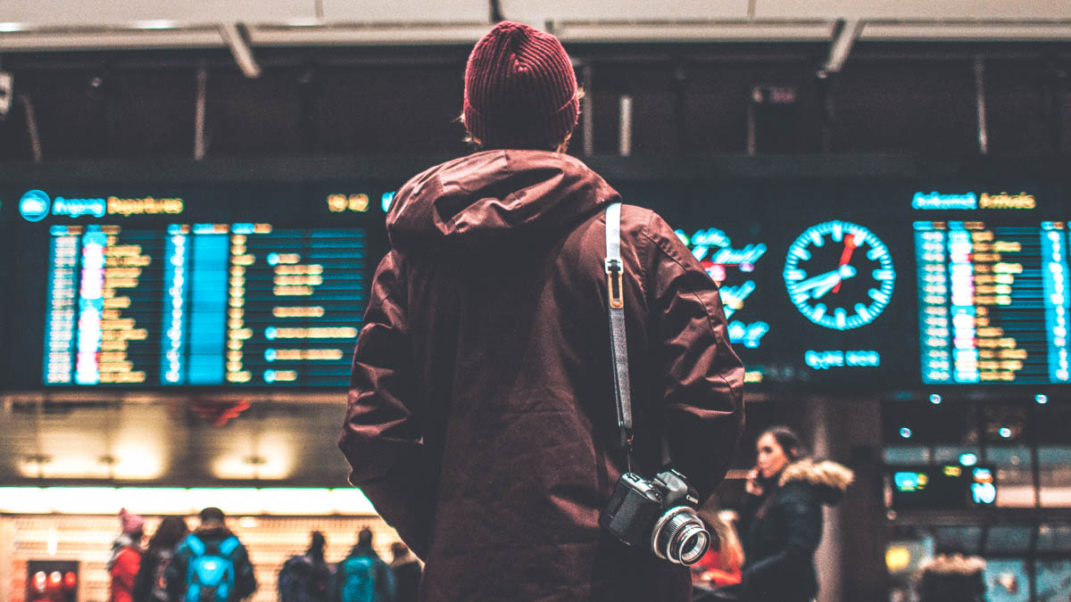 Man standing at airport looking for his flight departure