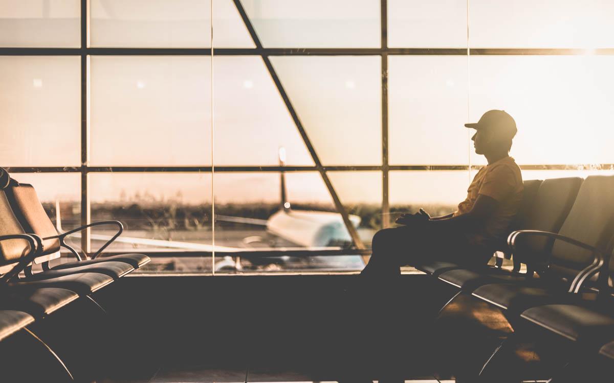 Man sitter och väntar på sitt flyg på flygplatsen