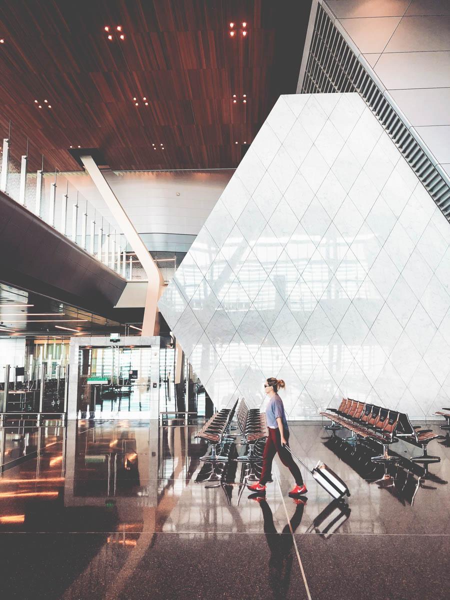 Kvinna går med resväska genom flygplatsen