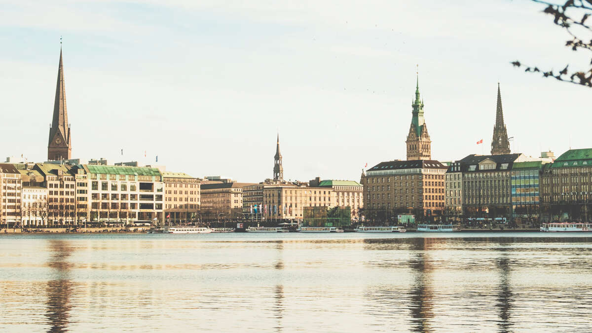 view of hamburg city from alster lake with reflections of the city in the surface of the water